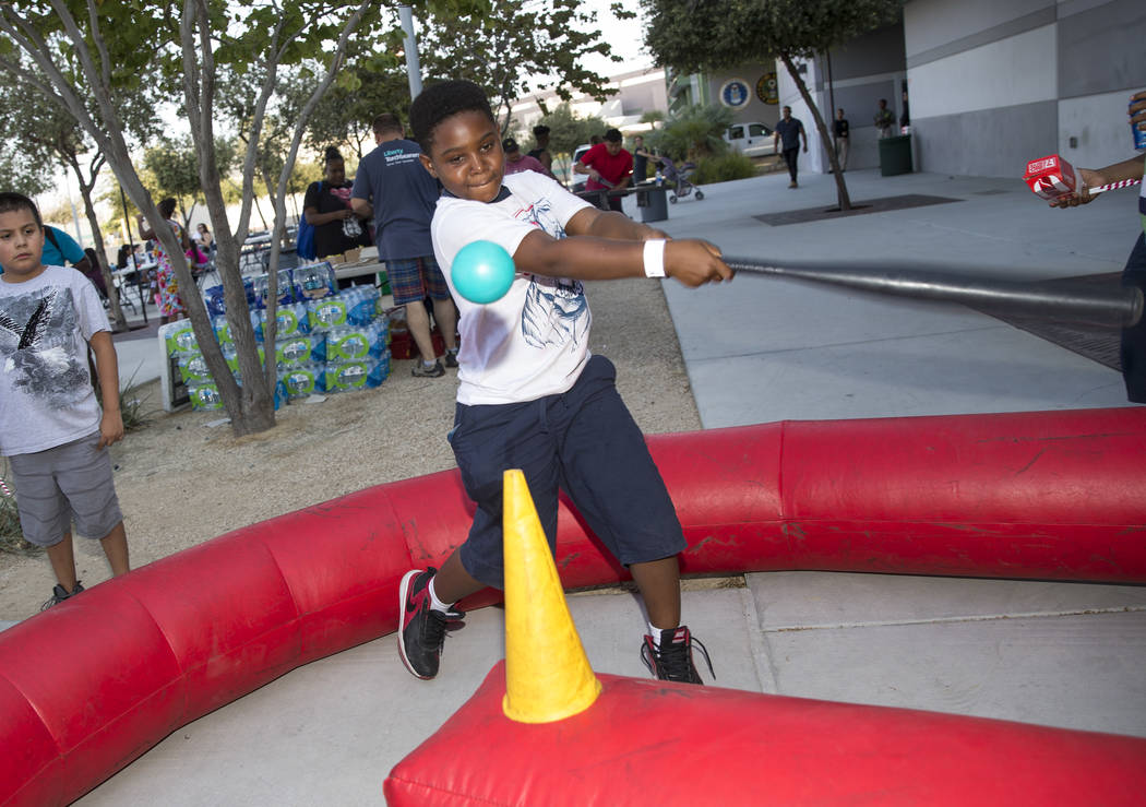 Las Vegas resident Zi'yon Williams, 9, takes a swing on an inflatable t-ball game during the Citywide Traffic Safety Block Party hosted by the Las Vegas Metropolitan Police DepartmentÕs traff ...