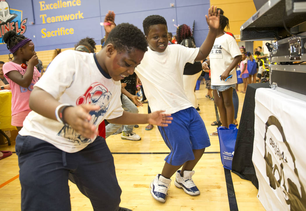 Nine-year-old cousins Zi'yon Williams, left, and B.J. Morris dance to the sounds of Drake during the Citywide Traffic Safety Block Party hosted by the Las Vegas Metropolitan Police Department&#xd5 ...
