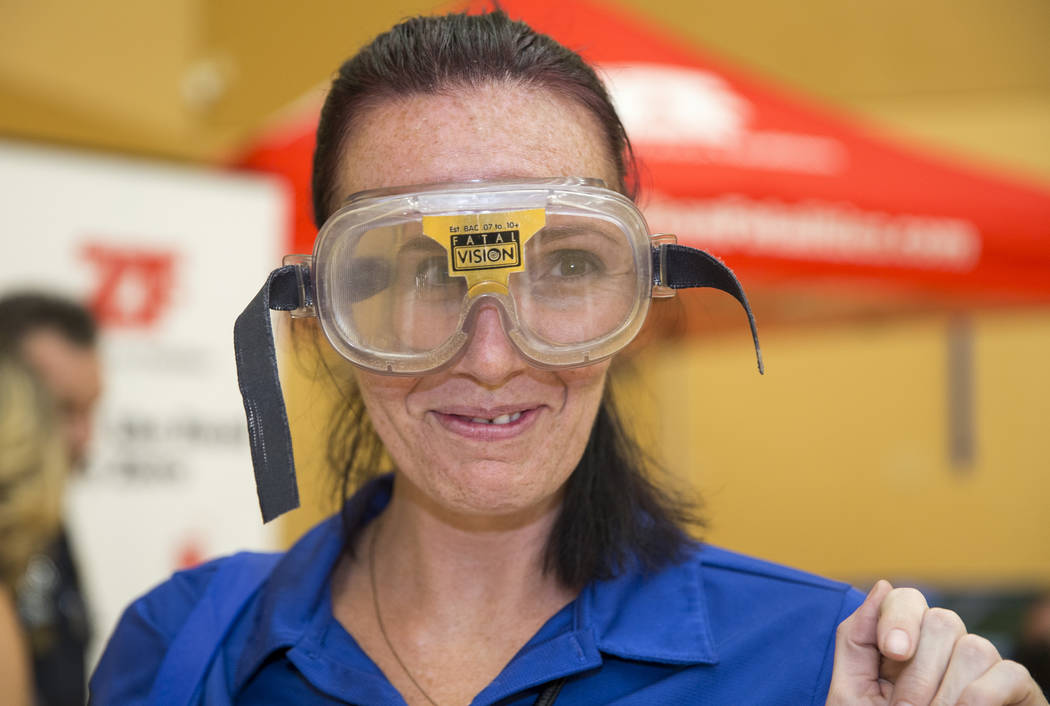 Las Vegas resident Teena Anthony demos the Fatal Vision goggles, customized goggles used to simulate alcohol impairment, at the Nevada Highway Patrol booth during the Citywide Traffic Safety Block ...