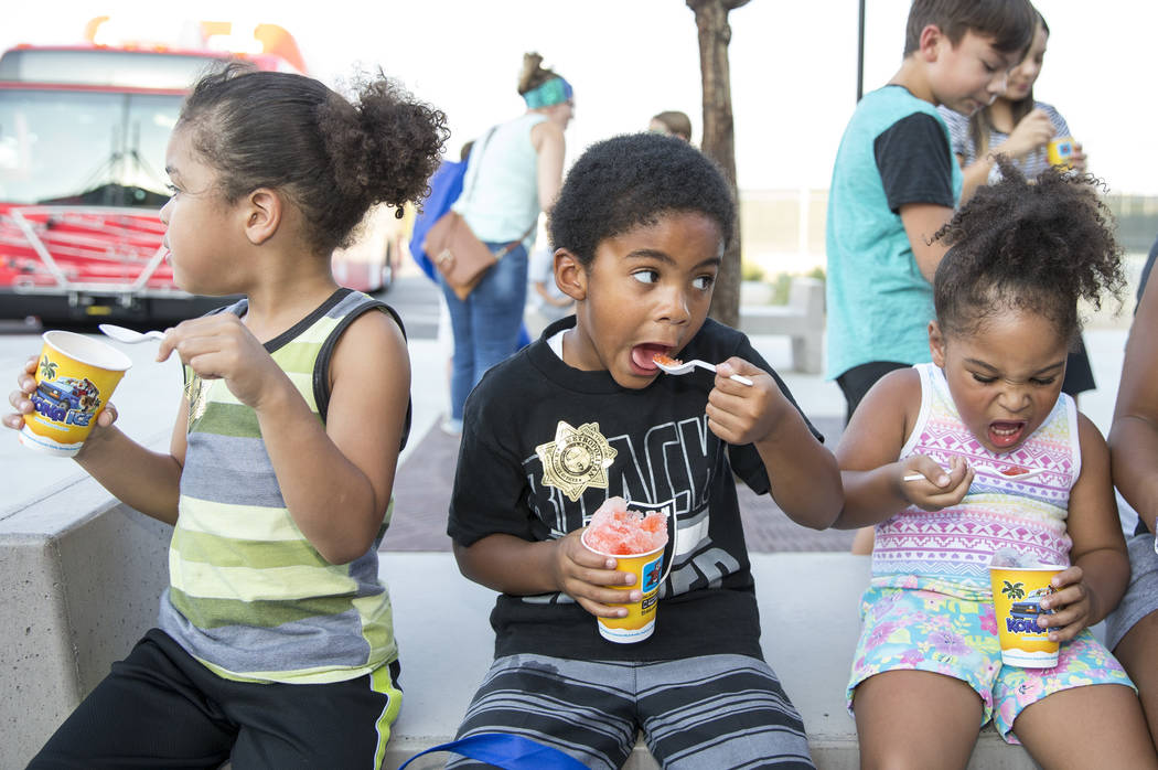 Trayden, 5, from left, Donothan, 5, and Anayah Nobriga, 3, cool off with snow cones during the Citywide Traffic Safety Block Party hosted by the Las Vegas Metropolitan Police DepartmentÕs tra ...