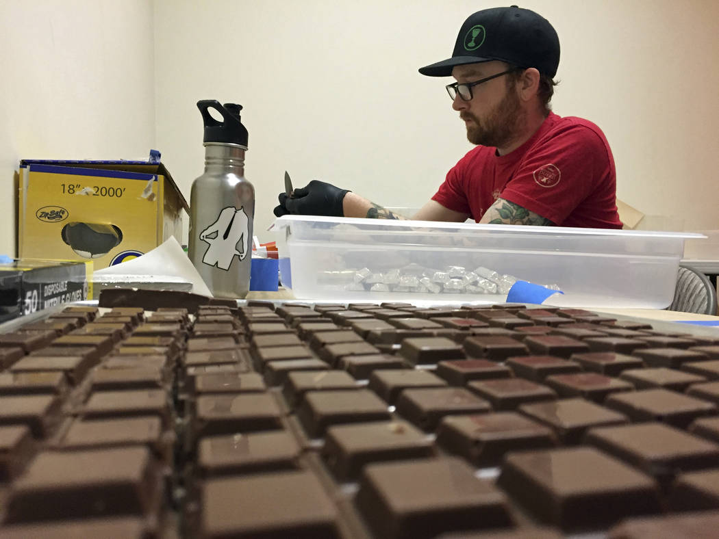 In this June 2, 2016 file photo, Chalice Farms production manager John Schuch wraps cannabis-infused hazelnut milk chocolates infused with marijuana in foil papers to prepare for sale at the compa ...