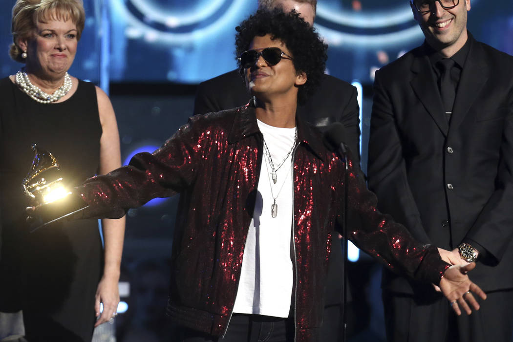 """Bruno Mars accepts the award for record of the year for """"24K Magic"""" at the 60th annual Grammy Awards in New York on Jan. 28, 2018. The Grammy Awards are extending the number of nominees in its top ..."""