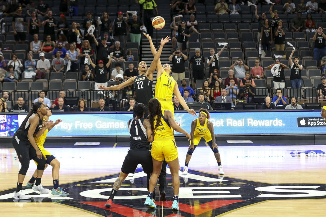 Las Vegas Aces center A'ja Wilson (22) and Indiana Fever forward Natalie Achonwa (11) tip off to start the first half of a WNBA basketball game at the Mandalay Bay Events Center in Las Vegas on Su ...