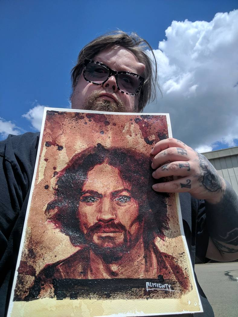 Artist Ryan Almighty shows a painting of Charles Manson, with Manson's ashes used for the eyes, before he shipped the piece to Zak Bagans' Haunted Museum on Saturday, July 28, 2018. (Zak Bagans' H ...