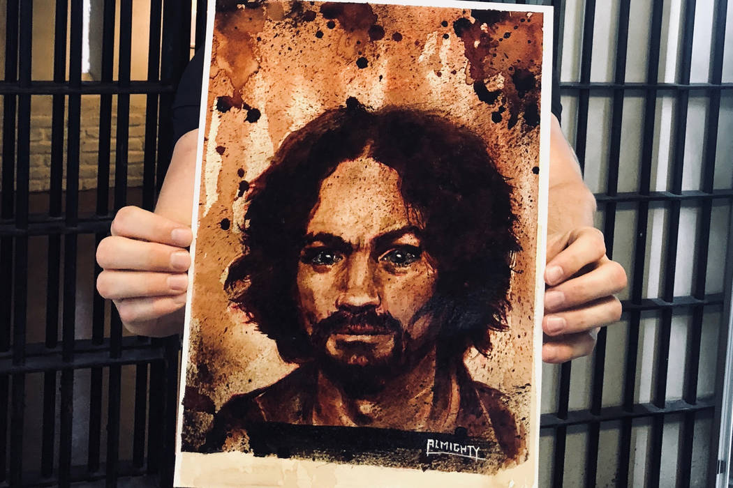 """Zak Bagans of """"Ghost Adventurers"""" on Travel Channel shows a painting of Charles Manson, with Manson's ashes used for the eyes, at Zak Bagans' Haunted Museum on Saturday, July 28, 2018. (Zak Bagans ..."""