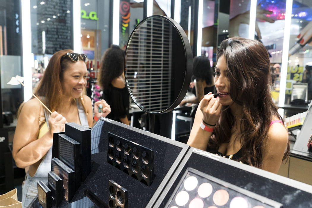 Jane Acero, left, browses MAC's selection while friend Michelle Lazo tries on some lipstick for National Lipstick Day at the Miracle Mile Shops in Las Vegas, Sunday, July 29, 2018. (Marcus Villagr ...