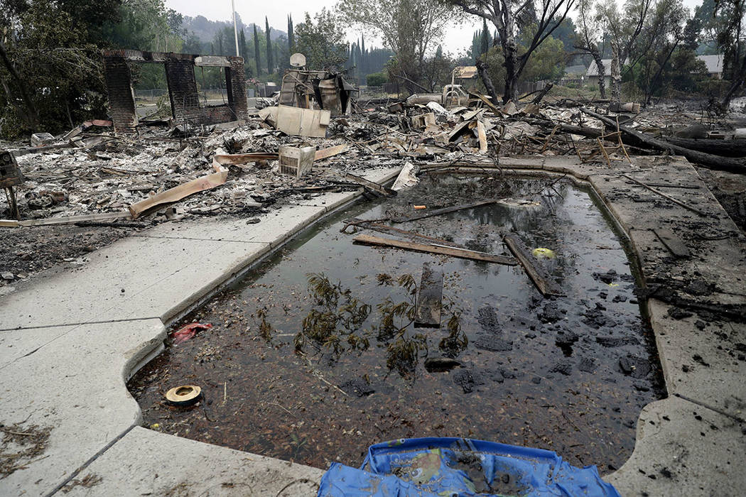 Debris and charred items litter a wildfire-ravaged home Saturday, July 28, 2018, in Redding, Calif. (AP Photo/Marcio Jose Sanchez)