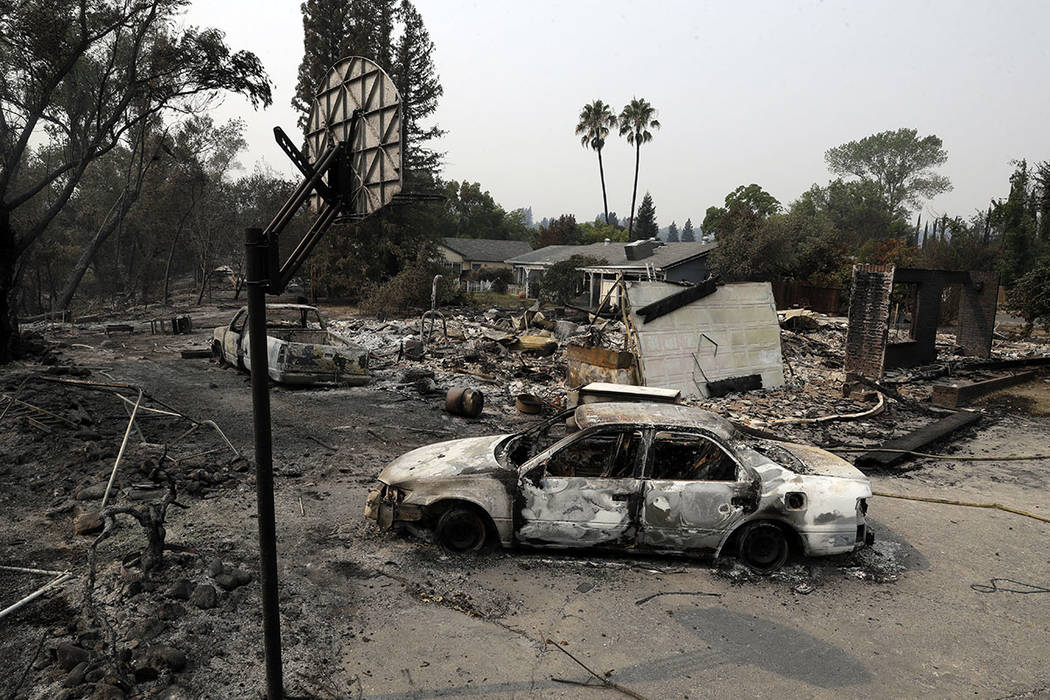 Burned vehicles are seen in front of a wildfire-ravaged home, Sunday, July 29, 2018, in Redding, Calif. (AP Photo/Marcio Jose Sanchez)