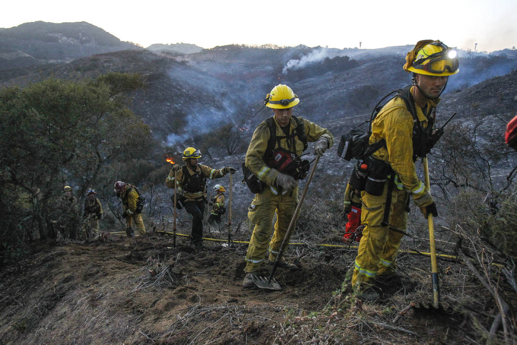 A hand crew of firefighters from various San Diego County fire departments scratch out a fire line after a brushfire burned in De Luz, Calif., on Saturday, July 28, 2018. (Hayne Palmour IV/The San ...