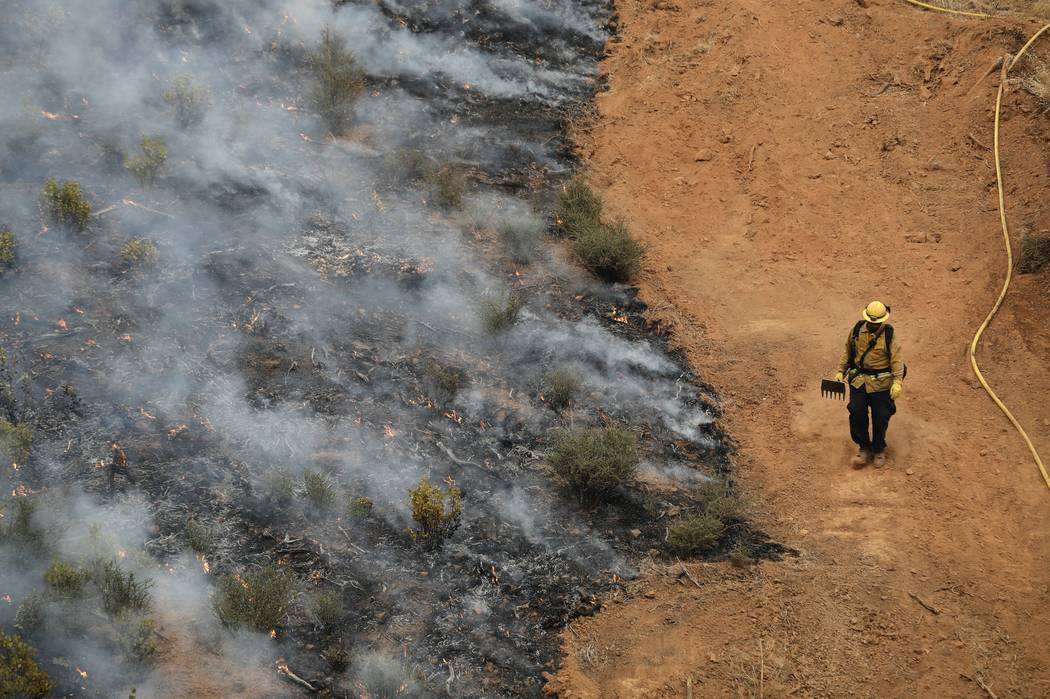 A firefighter walks along a containment line while battling a wildfire Saturday, July 28, 2018, in Redding, Calif. (AP Photo/Marcio Jose Sanchez)