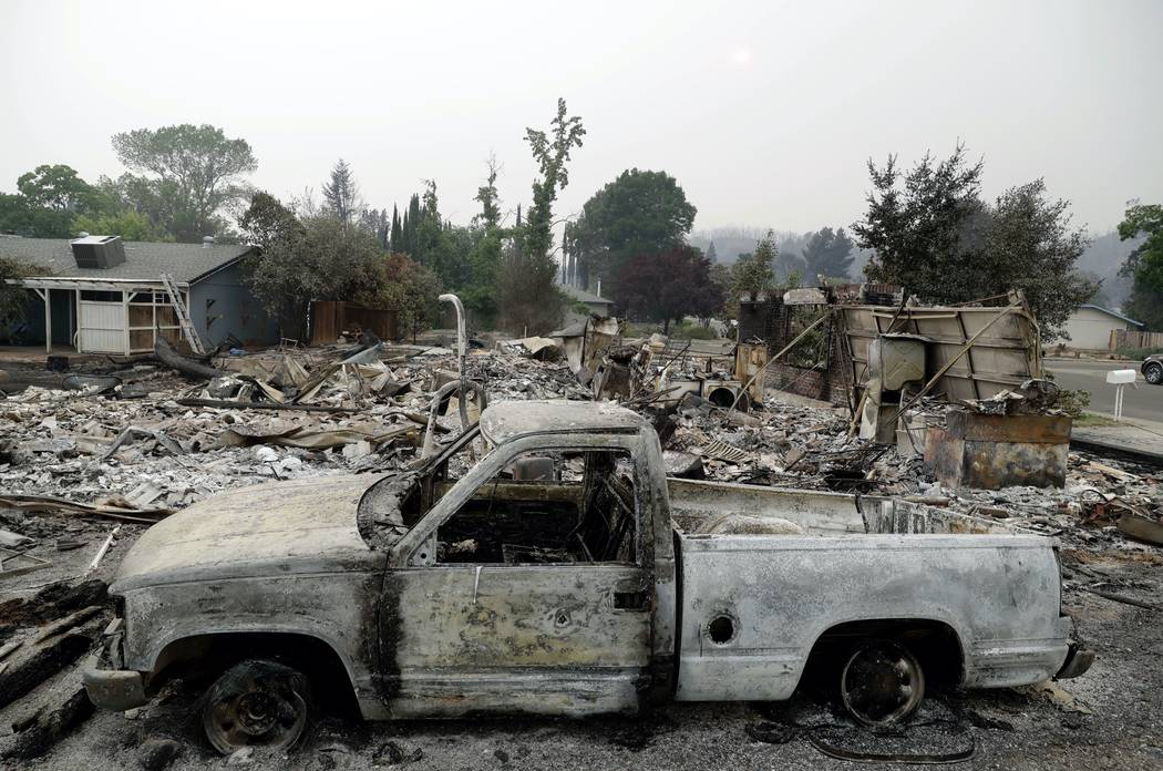 A burned down vehicle sits in front of a wildfire-ravaged home Saturday, July 28, 2018, in Redding, Calif. (AP Photo/Marcio Jose Sanchez)