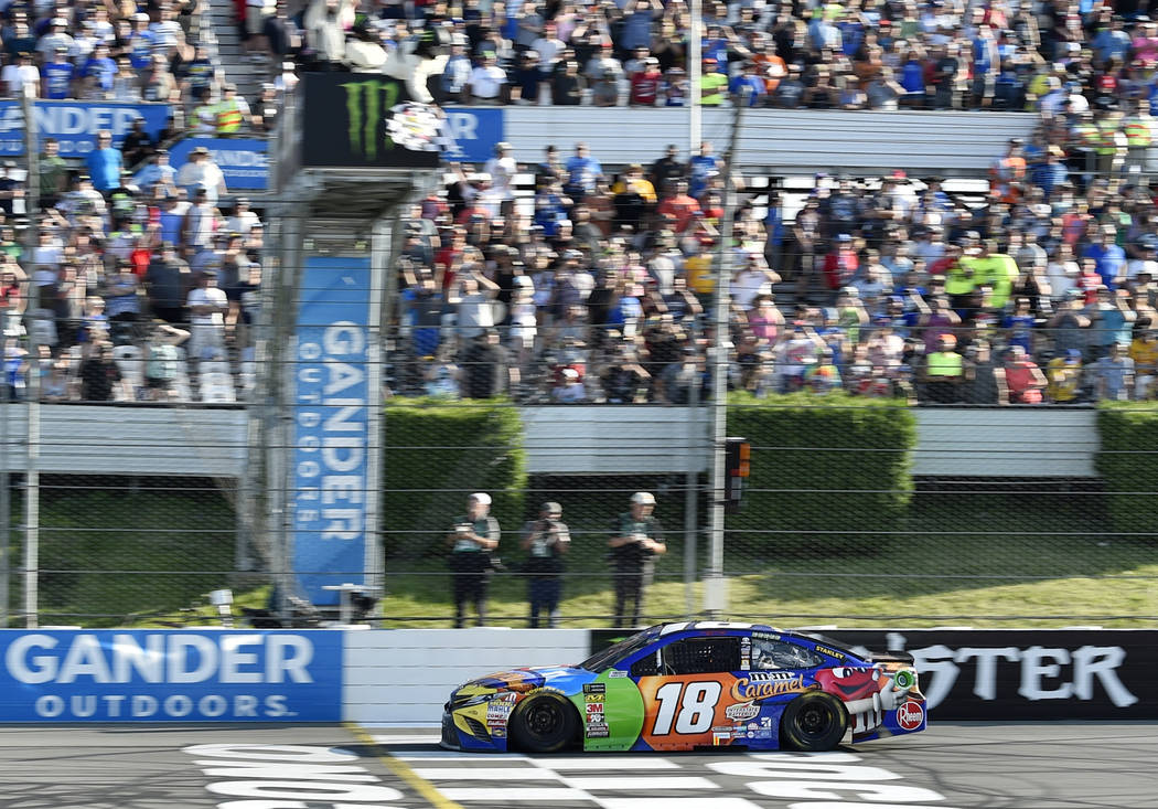Kyle Busch crosses the finish line to win a NASCAR Cup Series auto race, Sunday, July 29, 2018, in Long Pond, Pa. (AP Photo/Derik Hamilton)