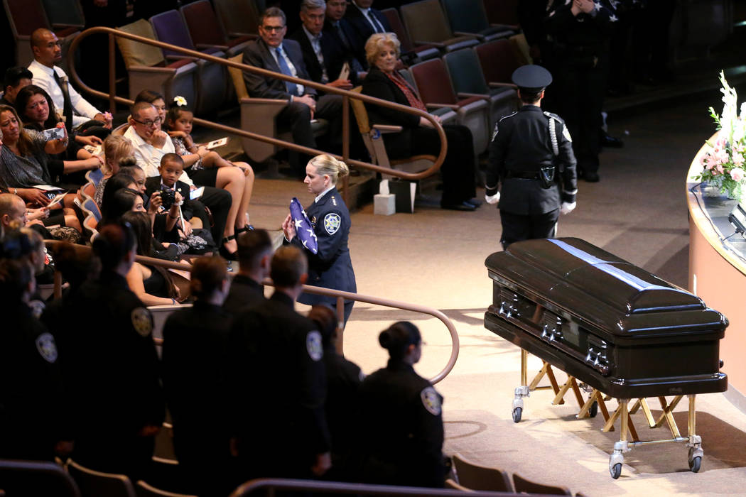 Michele Freeman, chief of Las Vegas Department of Public Safety, gives the American flag to widow Arlyn Eng during funeral services for Las Vegas Corrections Officer Kyle Eng at Canyon Ridge Chris ...