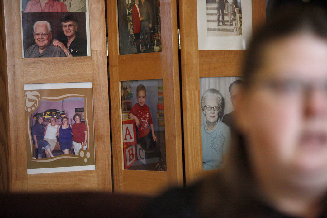 Photos of family and Daemion Olsen, center, behind Carrie Olsen as she talks about the health issues of her son to the Review-Journal at her home in Las Vegas, Tuesday, July 31, 2018. Medicaid ann ...