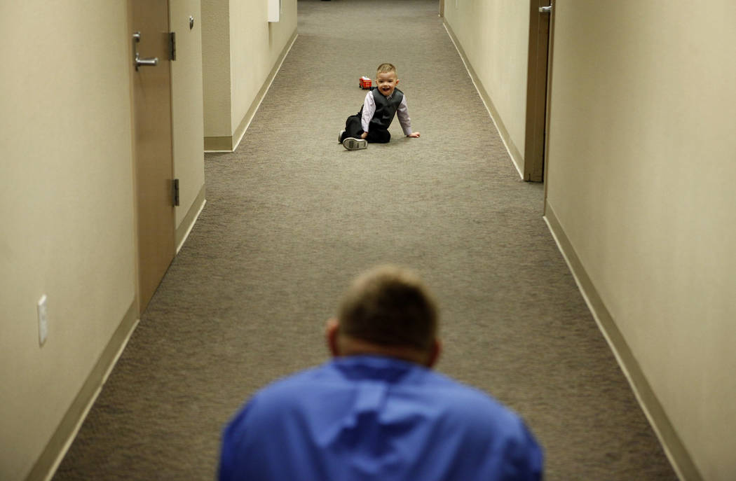 Three-year-old Daemion Olsen plays with his father Jeff Olsen, bottom, in a hallway at the Family Courts and Services Center in Las Vegas Tuesday, March 13, 2012. Jeff Olsen and his wife Carrie ha ...