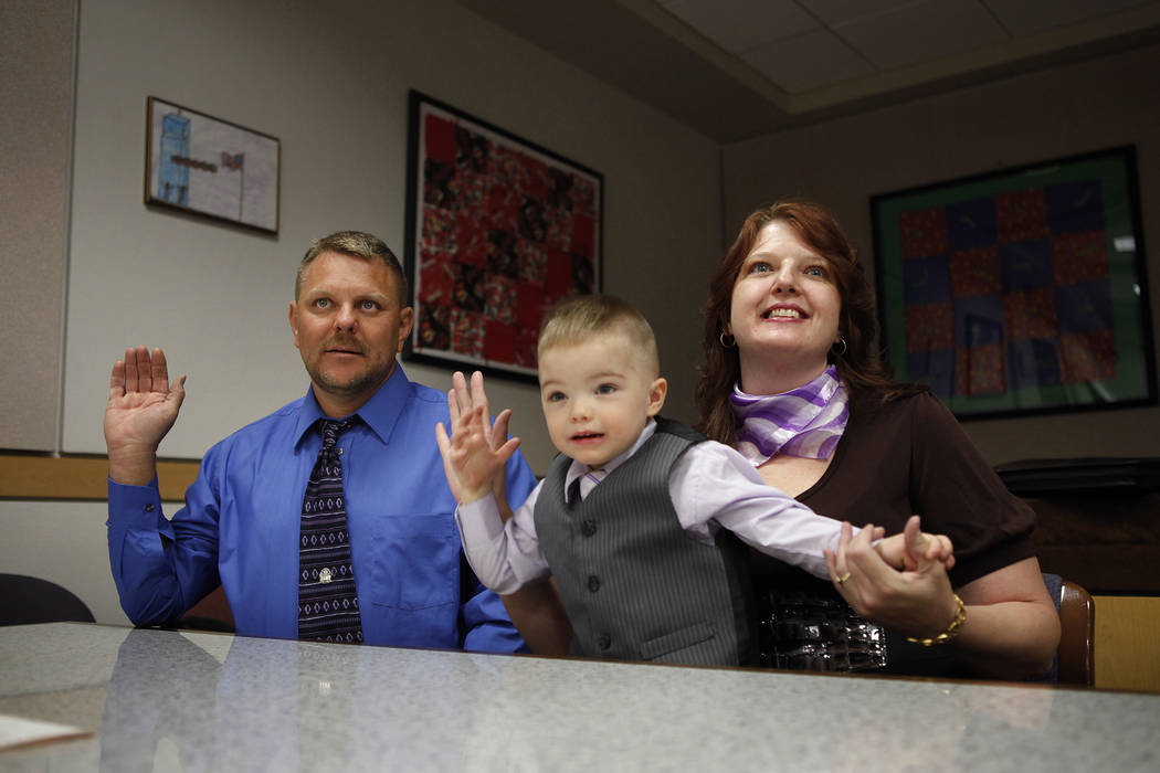 Three-year-old Daemion Olsen mimics his mother Carrie Olsen, right, and father Jeff Olsen as they are sworn-in during an adoption hearing at the Family Courts and Services Center in Las Vegas Tues ...