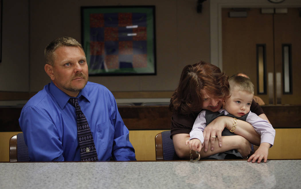 Three-year-old Daemion Olsen gets hugged by his mom Carrie Olsen as Jeff Olsen sits next to them during an adoption hearing at the Family Courts and Services Center in Las Vegas Tuesday, March 13, ...