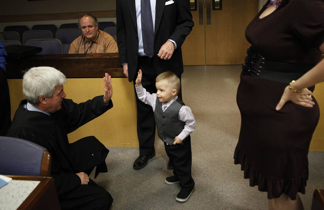Three-year-old Daemion Olsen, center, gives a high-five to Judge Frank P. Sullivan after an adoption hearing at the Family Courts and Services Center in Las Vegas Tuesday, March 13, 2012. Carrie a ...