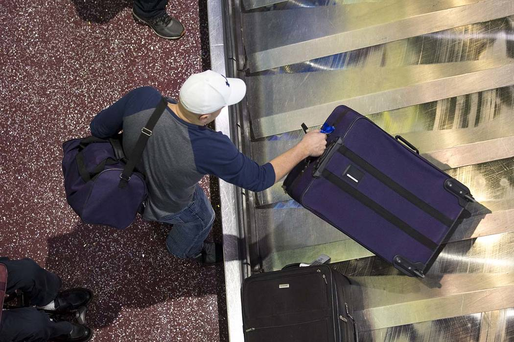 A man traveling on Allegiant grabs his belongings from baggage claim at Terminal 1 at McCarran International Airport in Las Vegas on Monday, April 16, 2018. Richard Brian Las Vegas Review-Journal ...