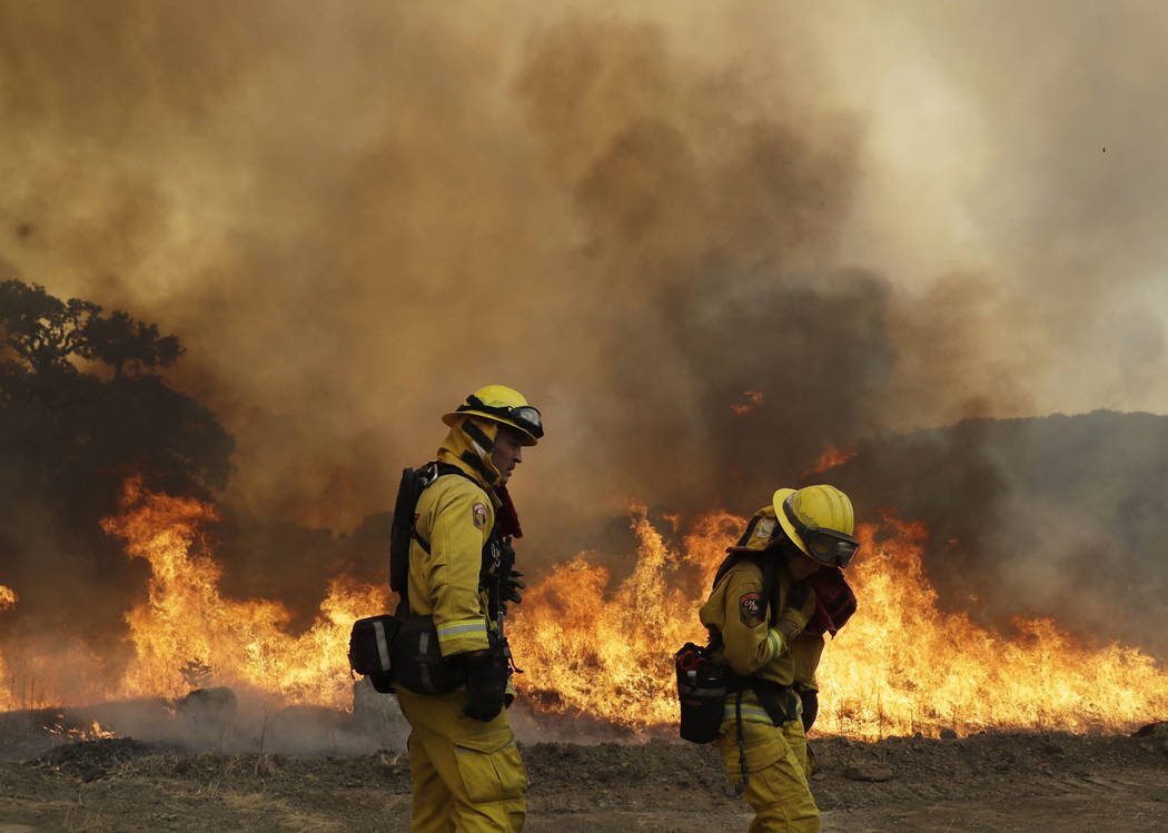 Firefighters with Cal Fire Mendocino Unit work the line as a wildfire advances Monday, July 30, 2018, in Lakeport, Calif. A pair of wildfires that prompted evacuation orders for thousands of peopl ...