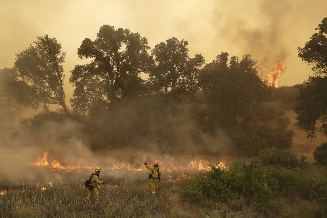 Firefighters with Cal Fire Mendocino Unit work the lines as a wildfire advances Monday, July 30, 2018, in Lakeport, Calif. A pair of wildfires that prompted evacuation orders for thousands of peop ...