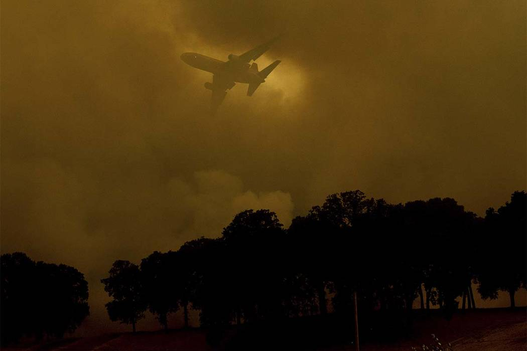 An air tanker passes behind a smoke plume while battling the River Fire in Lakeport, Calif., on Monday, July 30, 2018. A pair of wildfires that prompted evacuation orders for thousands of people a ...