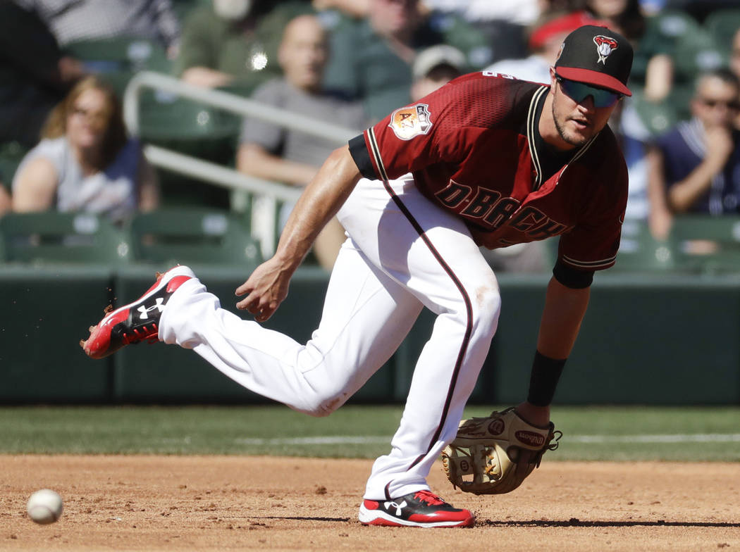 Arizona Diamondbacks third baseman Jack Reinheimer can't get a glove on a hit by San Diego Padres' Manuel Margot during the second inning of a spring baseball game in Scottsdale, Ariz., Thursday, ...