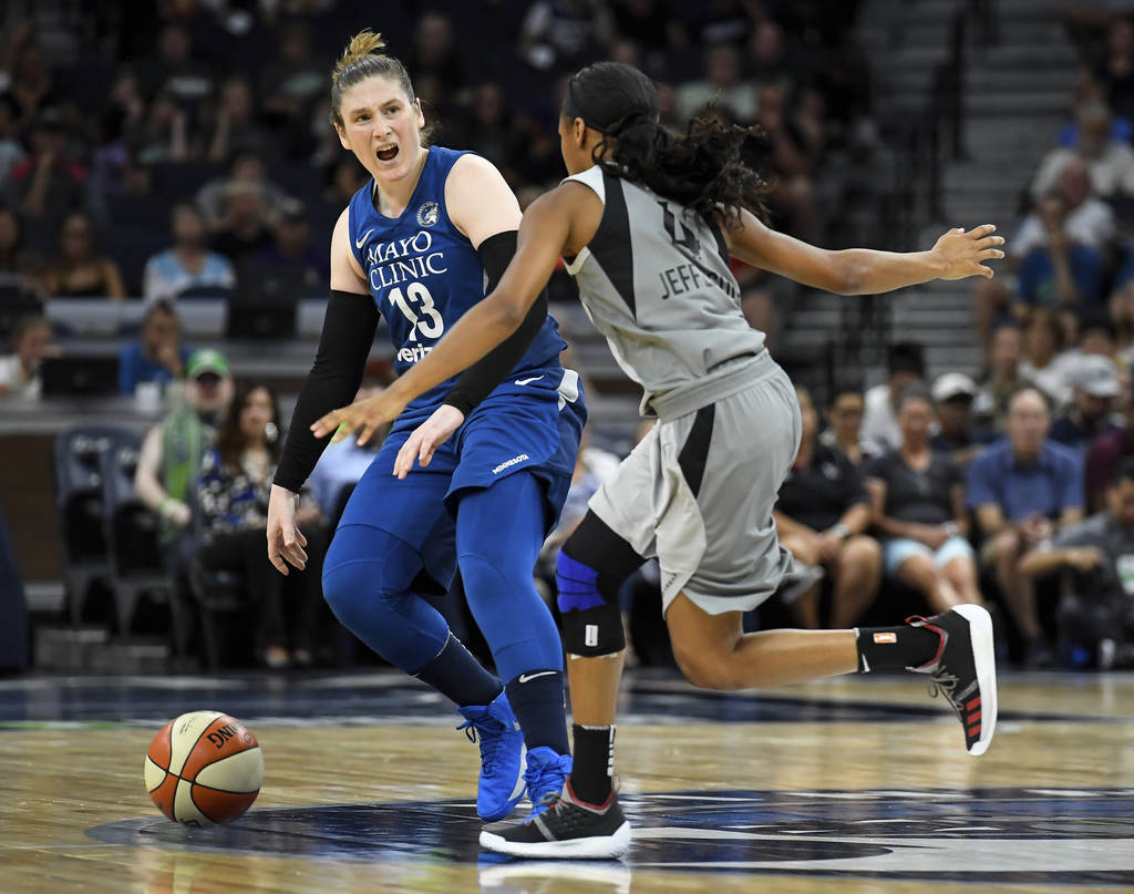 Minnesota Lynx guard Lindsay Whalen directs her teammates while moving the ball down the court under defense by Las Vegas Aces guard Moriah Jefferson (4) during the first half of a WNBA basketball ...