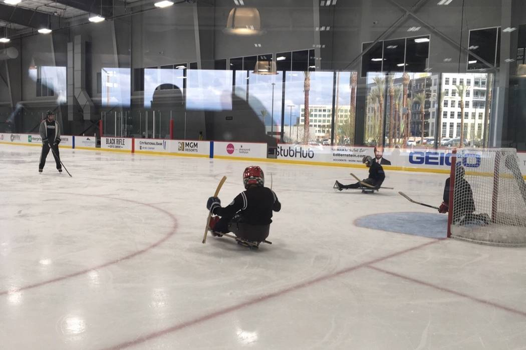 John Coogan, left, practices with sled hockey players at City National Arena. Courtesy: Gina Kielb/Jake Kielb Foundation.