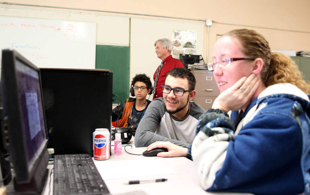 Gabbs schools students Timothy Howell, 13, left, and Jorge Martinez, 17, do course work online with the help of aide Crystal Howell, right, at the school Monday, April, 9, 2018. Standing at rear i ...