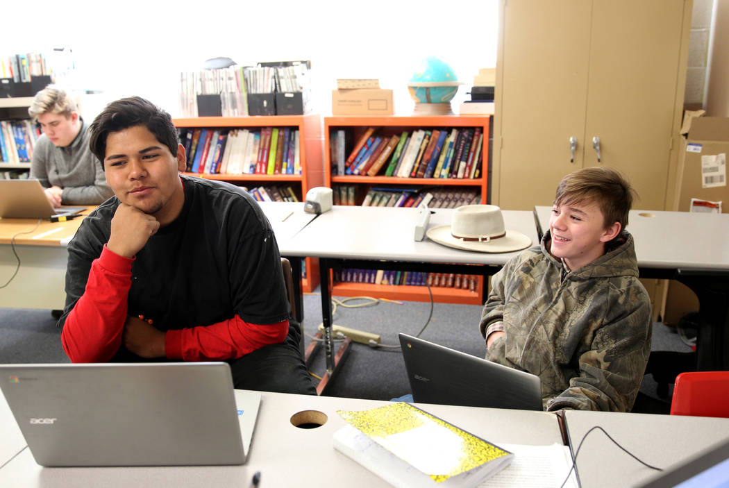 Gabbs schools students Dave Jim, a 15-year-old 10th grader, left, and Devin Gaither, a 13-year-old 8th grader visit while doing course work online at the school Monday, April, 9, 2018. K.M. Cannon ...