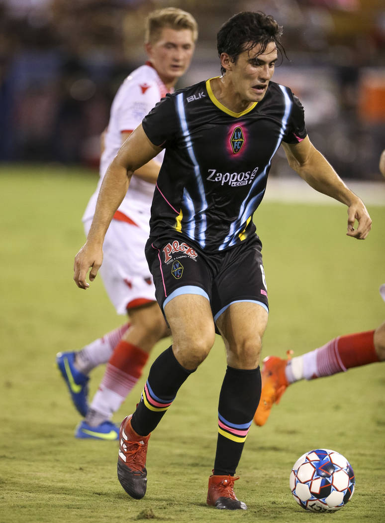 Light FC forward Omar Salgado (8) runs the ball against Phoenix Rising FC defenders during the first half of a United Soccer League match at Cashman Field in downtown Las Vegas on Saturday, August ...