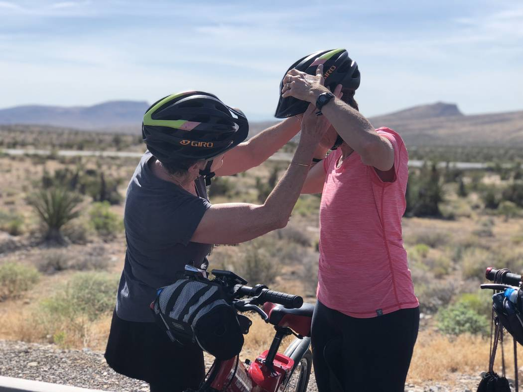 Janice Mangrum, left, helps her sister Monica Leo, right, adjust her helmet before their guided tour on electric bikes through the Red Rock Conservation Area on Friday, July 20, 2018. (Rio Lacanla ...