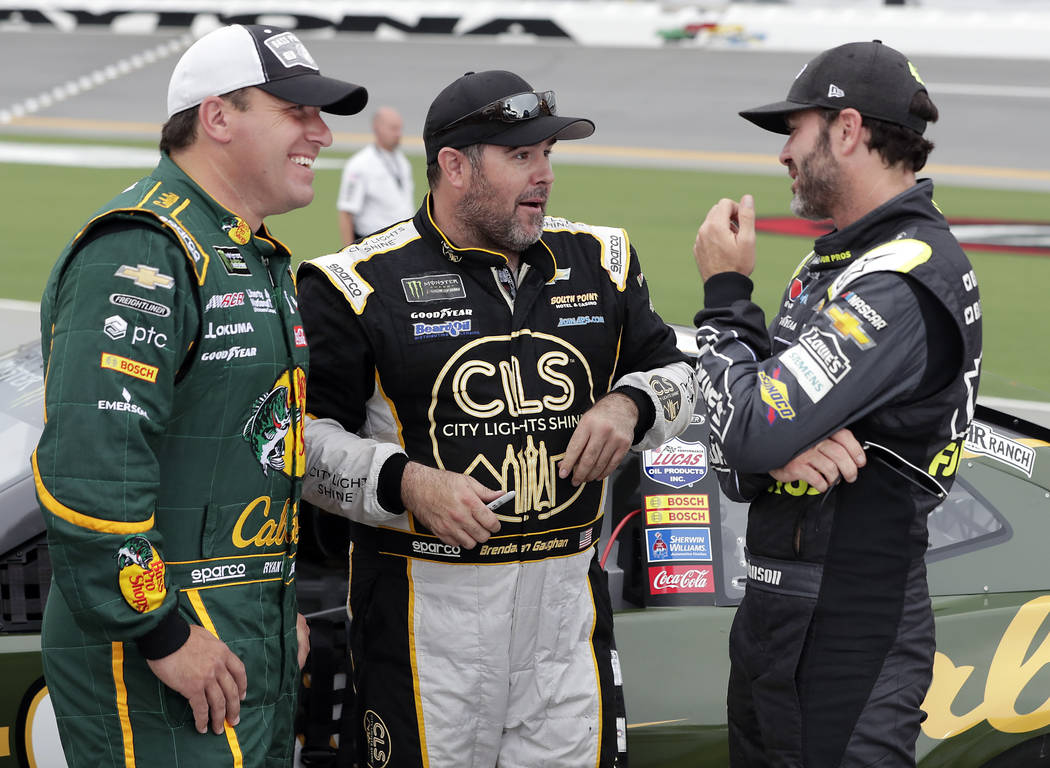 From left to right, Ryan Newman, Brendan Gaughan and Jimmie Johnson talk on pit road during qualifying for a NASCAR Cup Series auto race at Daytona International Speedway, Friday, July 6, 2018, in ...