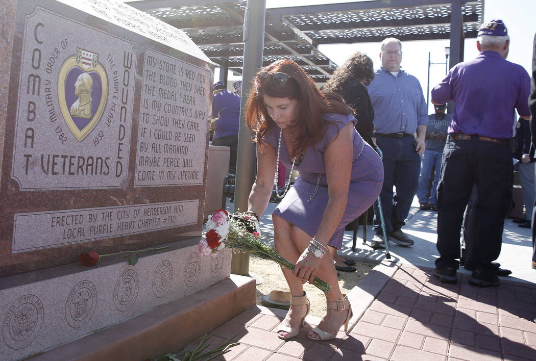 Henderson Mayor Debra March places a bouquet of flowers at Purple Heart Monument during the official opening of Purple Heart Plaza at 101 Market St. in downtown Henderson on Tuesday, Aug. 7, 2018. ...