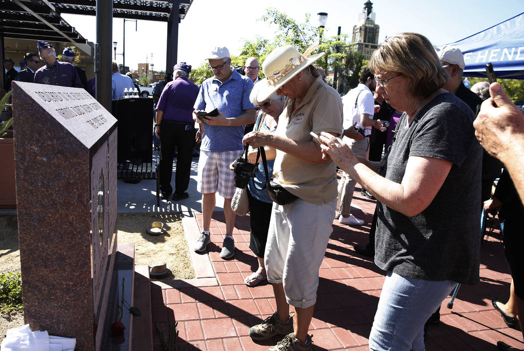 Diane Holman, right, and Dianne Robbins, both of Henderson, take a picture of Purple Heart Monument during the official opening of Purple Heart Plaza at 101 Market St. in downtown Henderson on Tue ...