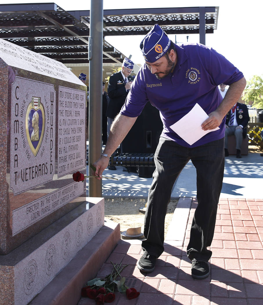 Chapter 730 Military of the Purple Heart Chaplin Raymond Warren places a rose at Purple Heart Monument during the official opening of Purple Heart Plaza at 101 Market St., in downtown Henderson on ...