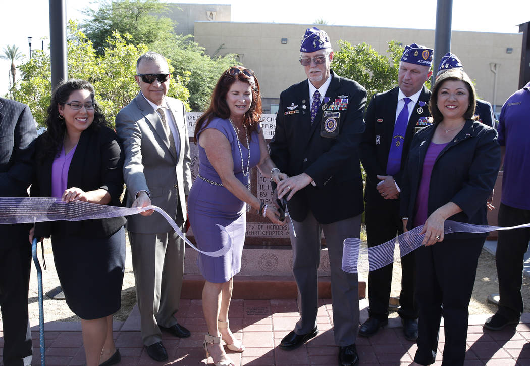 Henderson Mayor Debra March, center, and retired U.S. Army veteran David Hugus, third right, participate in the ribbon cutting ceremony for Purple Heart Plaza at 101 Market St. in downtown Henders ...