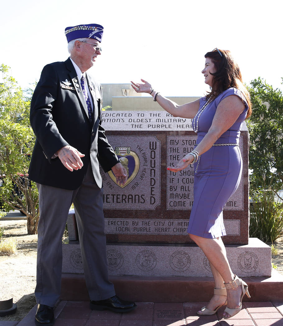 Henderson Mayor Debra March, right, greets retired U.S. Army veteran David Hugus after the official opening of Purple Heart Plaza at 101 Market St. in downtown Henderson on Tuesday, Aug. 7, 2018. ...