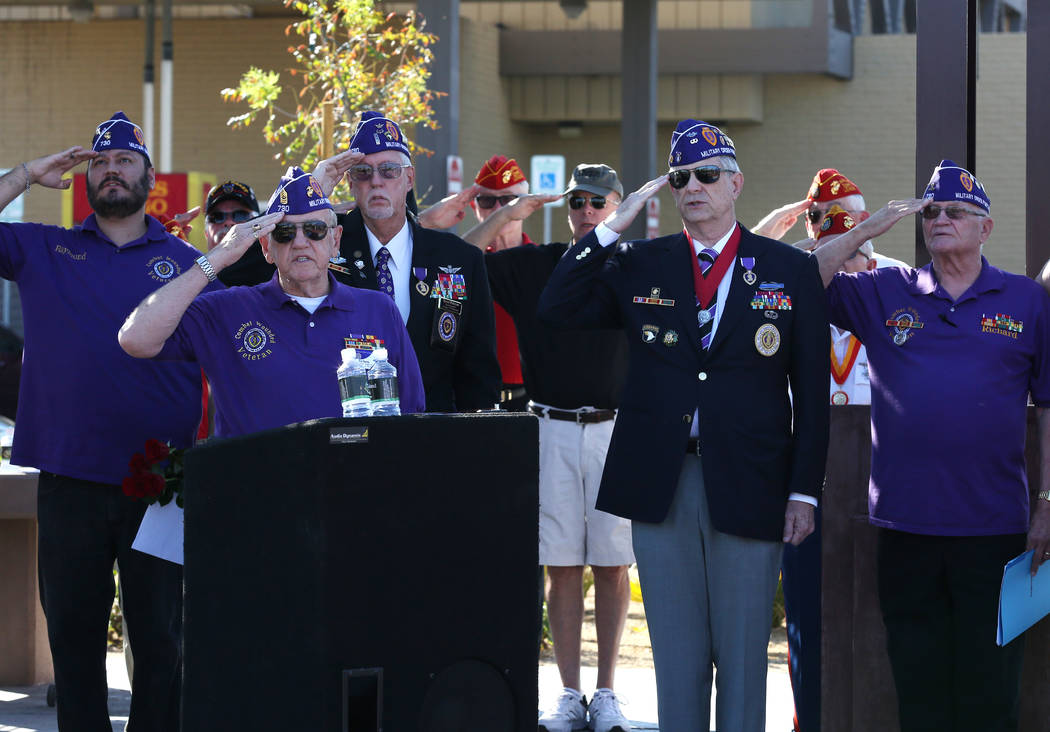 Members of Chapter 730 Military of the Purple Heart, including retired U.S. Army veteran David Hugus, second right, salute during the official opening of Purple Heart Plaza at 101 Market St. in do ...