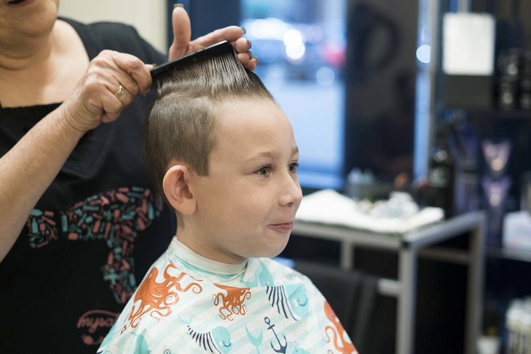 Sylas Fayne, a fourth-grader, gets a free haircut for his school supply donation at My Salon Suite in Las Vegas, Sunday, Aug. 5, 2018. (Marcus Villagran/Las Vegas Review-Journal) @brokejournalist