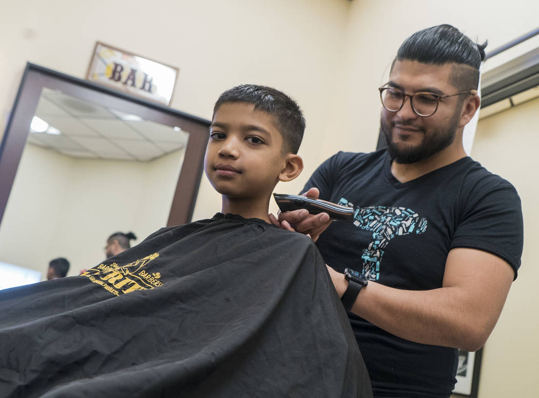 Bhaumik Jain, 5th grade, gets a free haircut from stylist Truman Gallegos at My Salon Suite in Las Vegas, Sunday, Aug. 5, 2018. My Salon Suite gives free haircuts to kids who donate school supplie ...