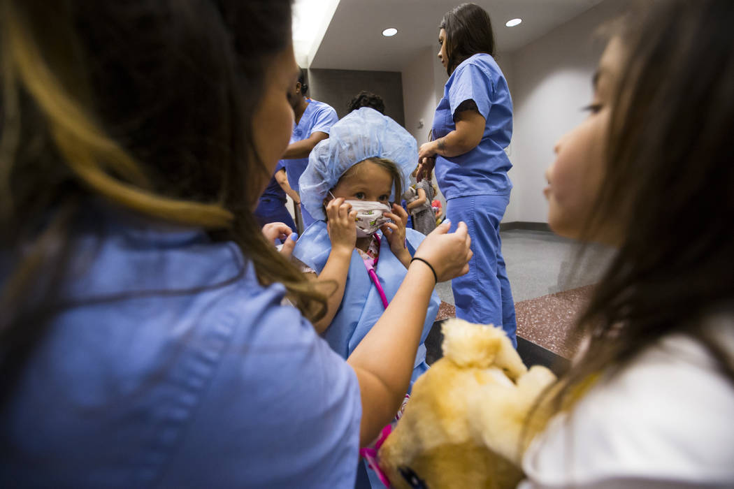 Lola Correa, 4, puts on a mask after getting dressed with scrubs during the Teddy Bear Clinic event at Centennial Hills Hospital in Las Vegas on Wednesday, Aug. 1, 2018. Chase Stevens Las Vegas Re ...