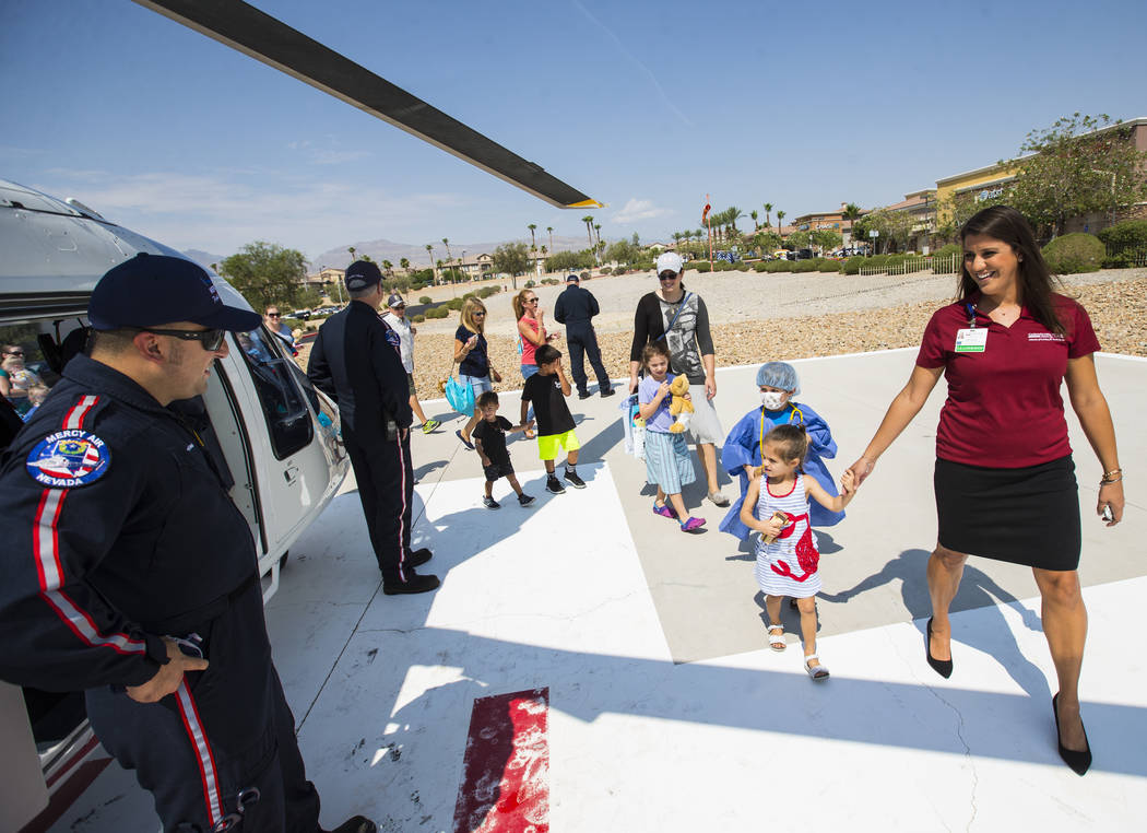 Erin Klein, director of business development at Centennial Hills Hospital, walks with daughter Maggie, 3, to look at a Mercy Air helicopter during the Teddy Bear Clinic event at Centennial Hills H ...