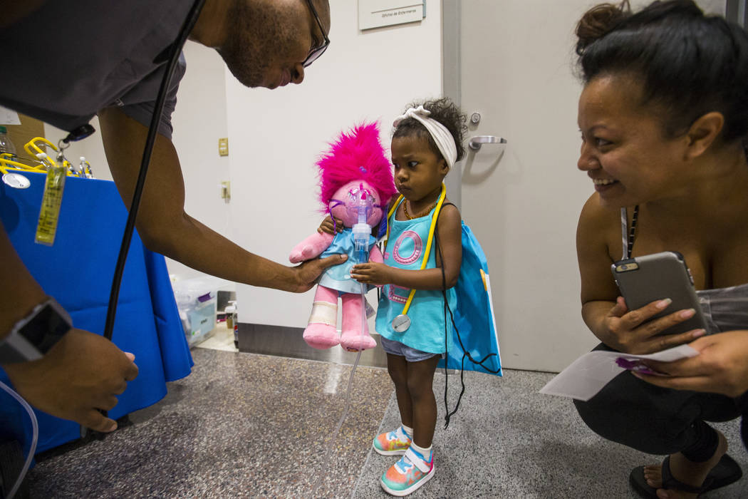Shannon Valencia of Las Vegas, right, watches her daughter Zariah Rouzan,2, interact with respiratory student Darrael Robinson during the Teddy Bear Clinic event at Centennial Hills Hospital in La ...