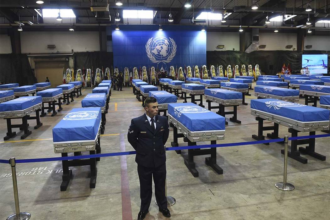 A U.S. airman stands guard next to caskets containing remains of U.S. soldiers killed in the Korean War and collected in North Korea before a repatriation ceremony at Osan Air Base in Pyeongtaek o ...