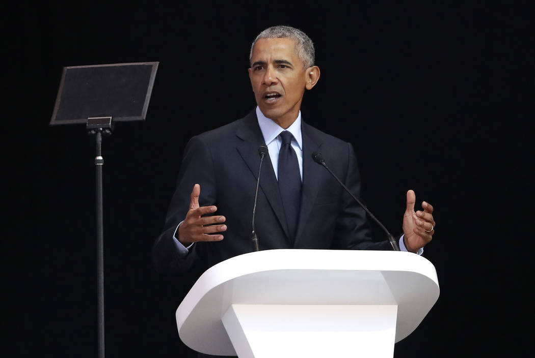Former U.S. President Barack Obama, left, delivers his speech at the 16th Annual Nelson Mandela Lecture at the Wanderers Stadium in Johannesburg, South Africa, Tuesday, July 17, 2018. (Themba Hade ...