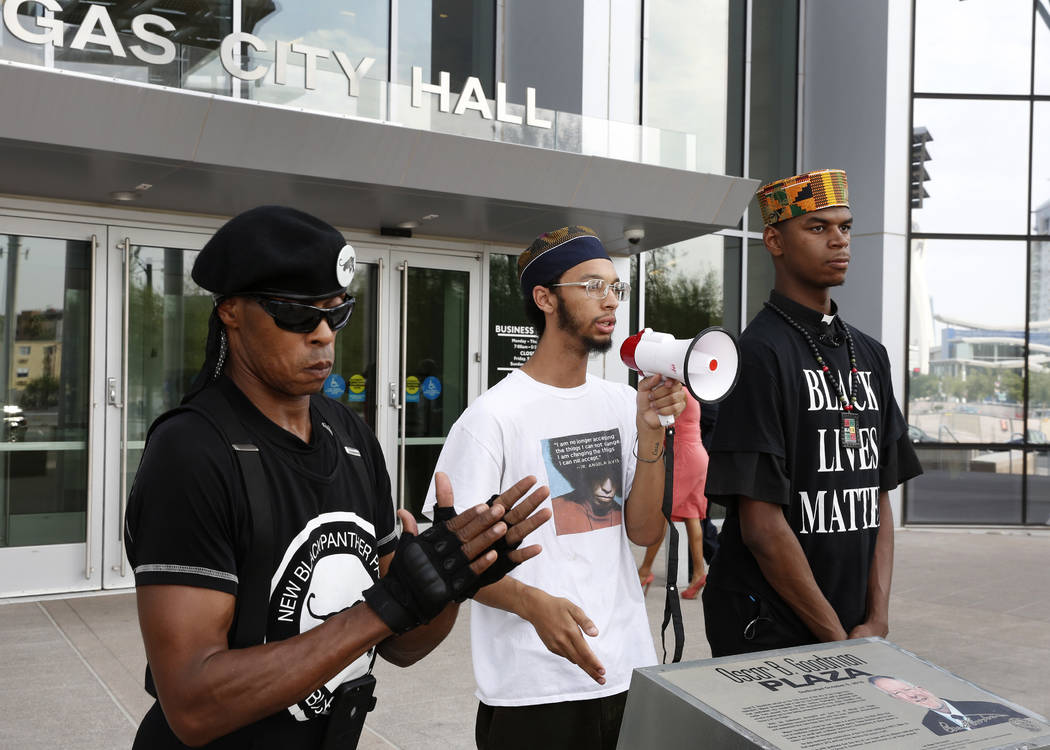 Local organizers Jay Jackson, left, and Minister Stretch Sanders, right, listen outside Las Vegas City Hall as Tre'Shawn Terry speaks to the media about police brutality on Wednesday, Aug. 1, 2018 ...
