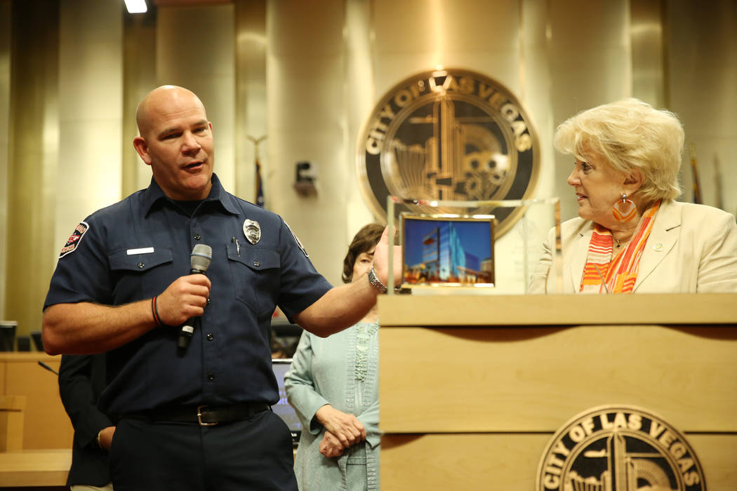 Las Vegas paramedic Matthew Driscoll, left, with Mayor Carolyn Goodman, is recognized as the employee of the month, during a city council meeting at Las Vegas City Hall in Las Vegas, Wednesday, Au ...