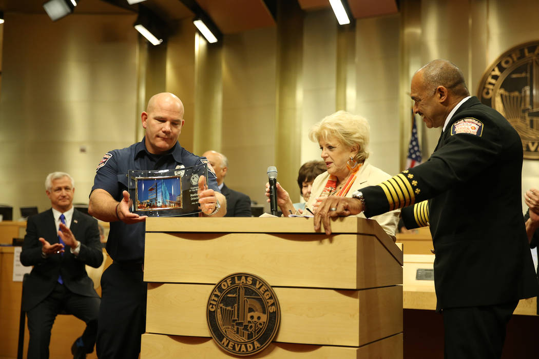 Las Vegas Mayor Carolyn Goodman, center, with Las Vegas Fire and Rescue Chief William McDonald, right, recognize paramedic Matthew Driscoll as the employee of the month, during a city council meet ...
